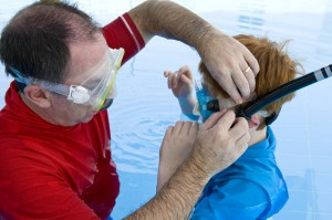 father helping child with snorkel gear